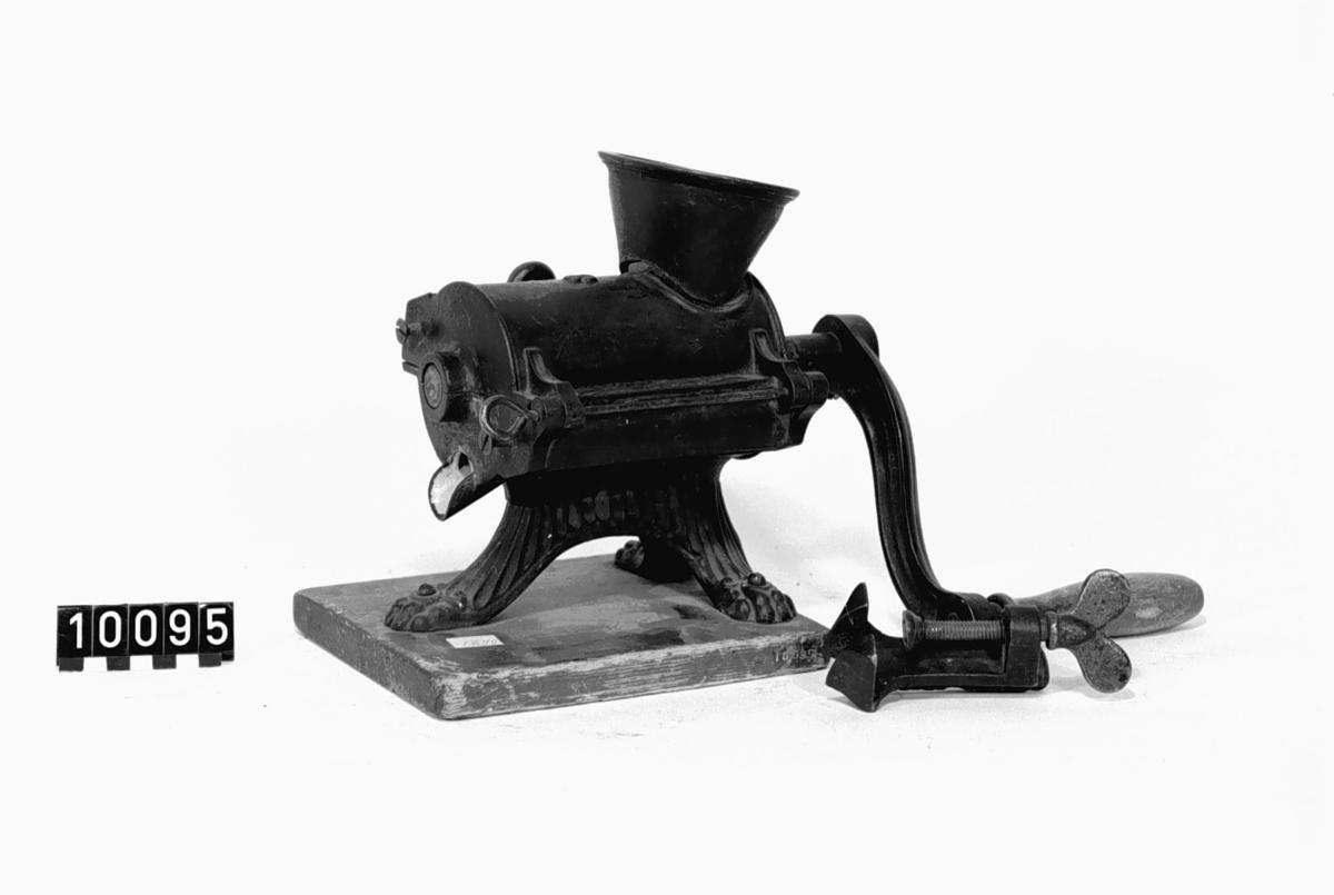Köttkvarn av gjutjärn, på tre ben, fastsatt på en platta av trä. Invändigt emaljerad, mönstrad utanpå. Tillbehör: Tving