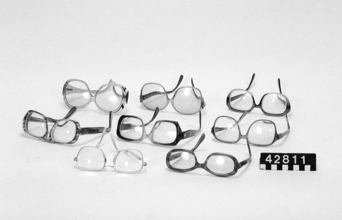 8 par glasögon av plast och glas. Måtten avser de största glasögonen. Glasögonen har bjärta, klara färger och stora ögonöppningar, typiska för tiden. Filos, 3 Christian Dior, Beatrice, Silhouette, Roodenstock Torro WD, ett par utan märkning.