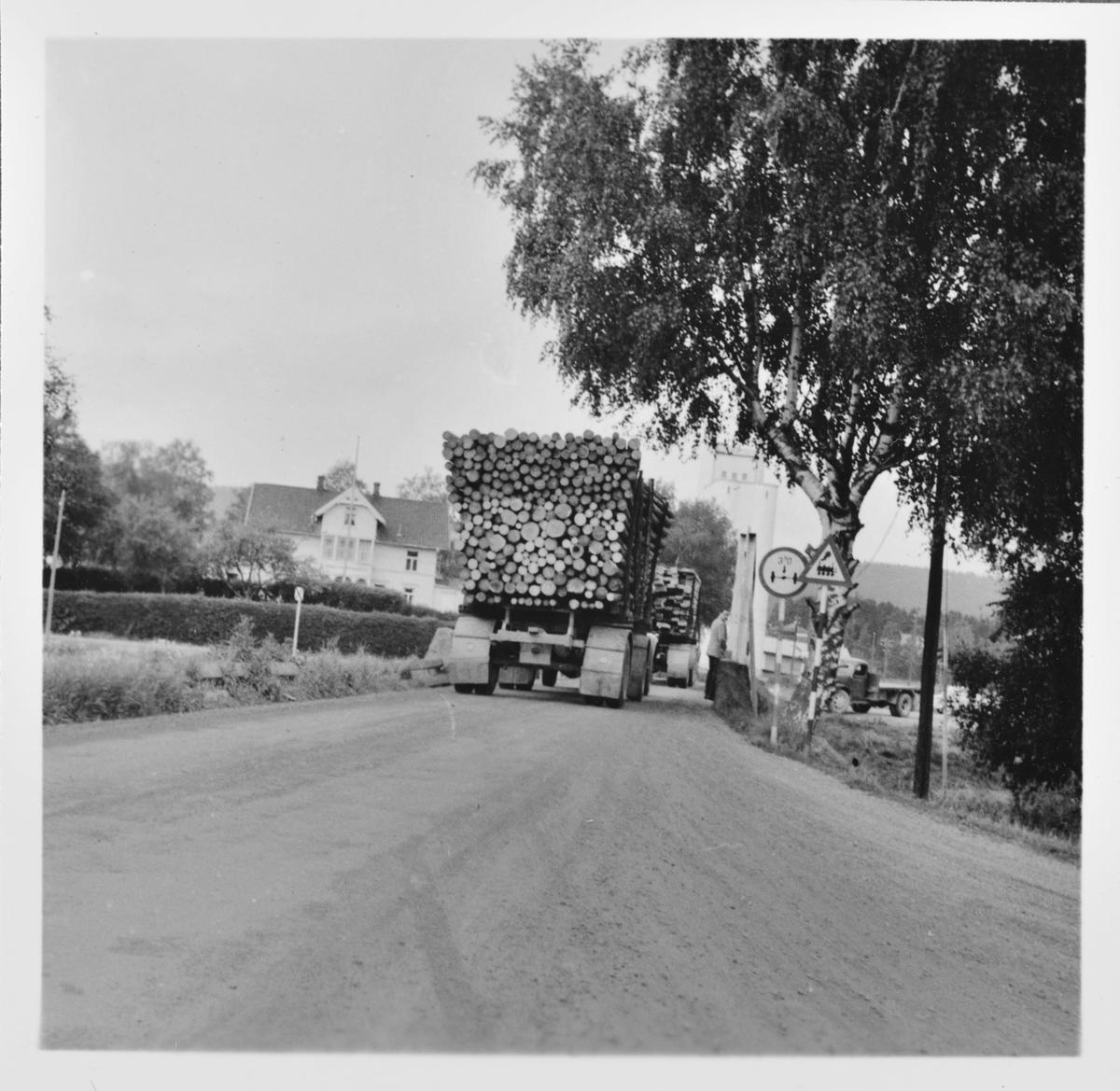 Tømmerbil passerer Kjelle bro på Bjørkelangen. Tømmertransporten ble overtatt av lastebiler etter Urskog-Hølandsbanens nedleggelse 30.6.1960.