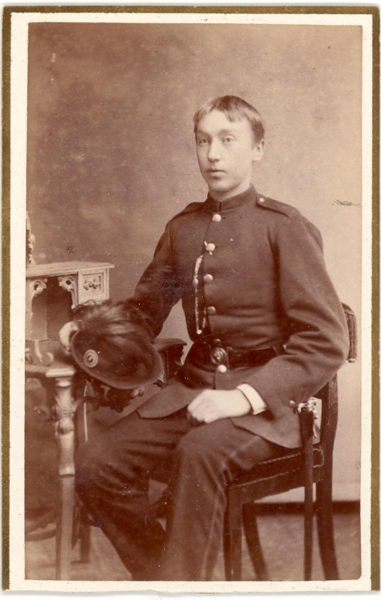 Brystbilde av Olav H. Fossheim, Bø, som ung mann i militæruniform.