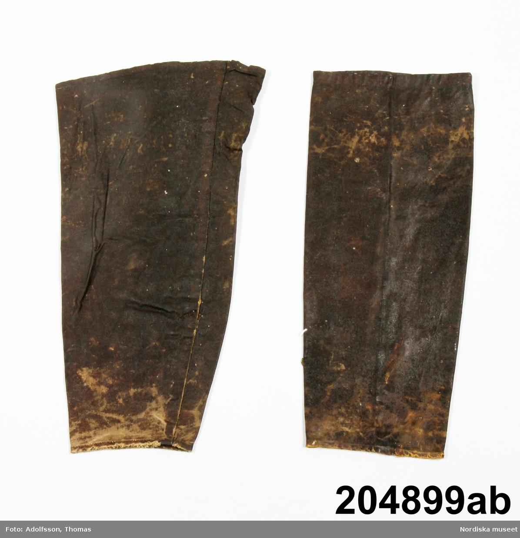 Ett par långa ärmholkar av mörkbrun oljeduk, av segelduk i bomull impregnerat med linolja,. nm. Något slitna i nederkant, stela av oljan. Har tillhört fiskaren Olov Karlsson från Rörö. Se även sydväst av samma tyg. /Berit Eldvik 2012-12-18