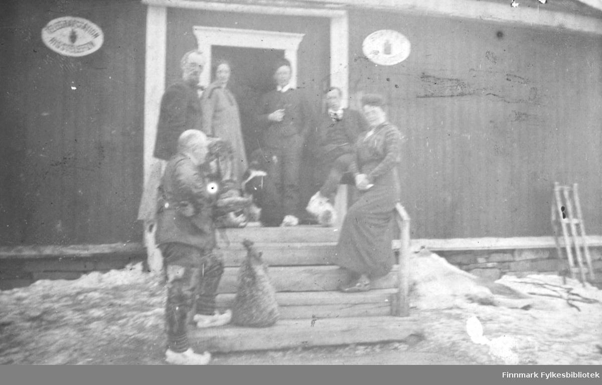 På trappa til Levajok fjellstue i april 1916. Seks personer og en hund er avbildet.  På veggen henger det to skilt. skiltet til venstre har teksten 'TELEGRAFSTATIONEN RIGSTELEFON' og på det til høyre står det 'STATENS FJELDSTUE' Ved siden av trappen står det en kjelke. Mannen i forgrunnen har skaller med skallebånd på beina.
