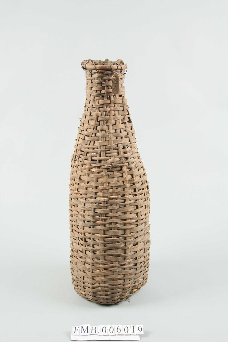 Laget av flettverk. Flaskeformet med en utsvingt åpning.