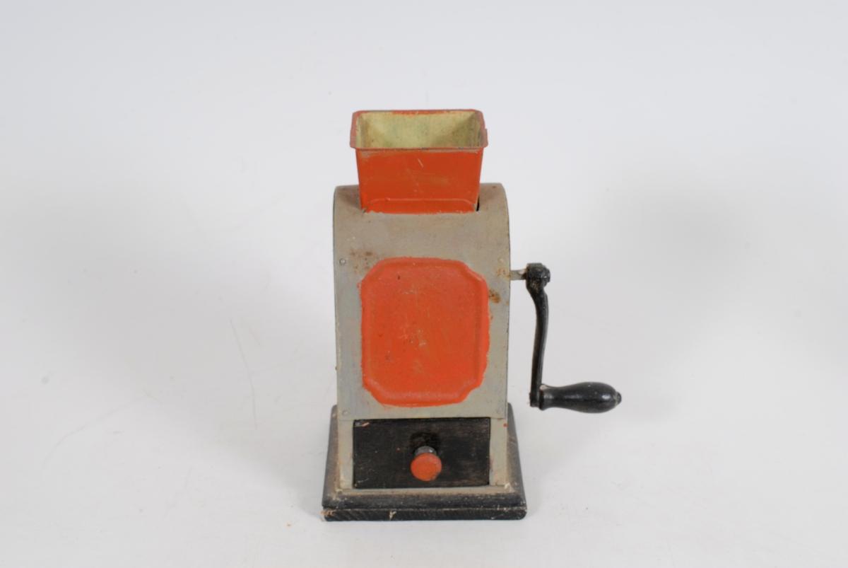 Form: Nederst på fremsiden en uttrekkbar skuff. Farge: A: Grå m/røde felter på frem og bakside. Rød trakt. Sort sveiv m/håndtak og fot. B: Grå og sort m/rød knott. Kjeller på Tømte.