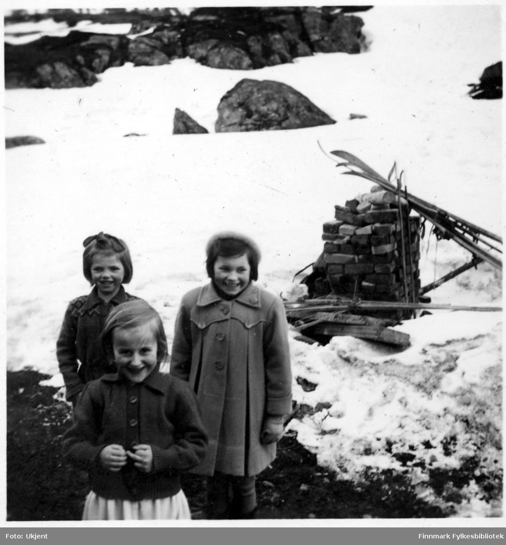 Jerlaug og Karin Andersen står bak Randi Martinsen (framst) og smiler til kameraet. Alle barna er fra Nuvsvåg. Jerlaug og Karin er kledd i jakker. Jerlaug har en sløyfe i håret, Karin en lue på hodet. Randi har på seg en genser. I bakgrunnen kan man se ski som er stablet opp, steiner og mye snø. Bildet er mulignes tatt i 1952.