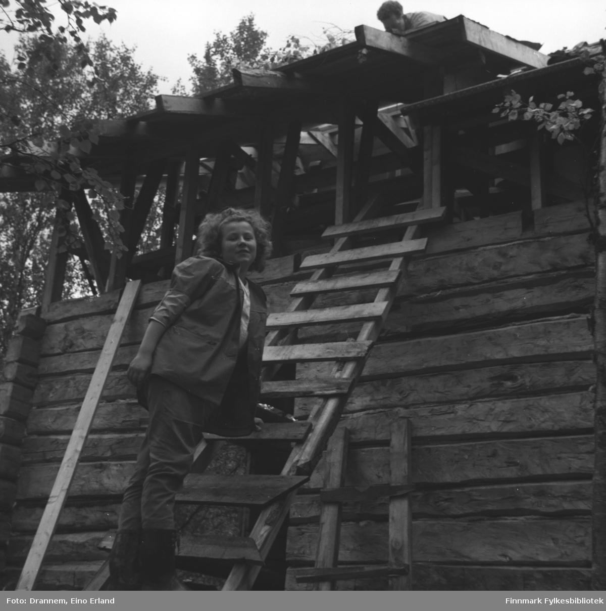 En hytte er under bygging eller renovering. Turid Karikoski klatrer opp stigen og en ukjent mann jobber på taket.