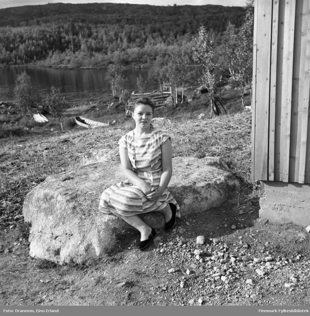 En ung dame sitter på en stor, flat stein iført sommerkjole. Hun heter Maija, ukjent etternavn.