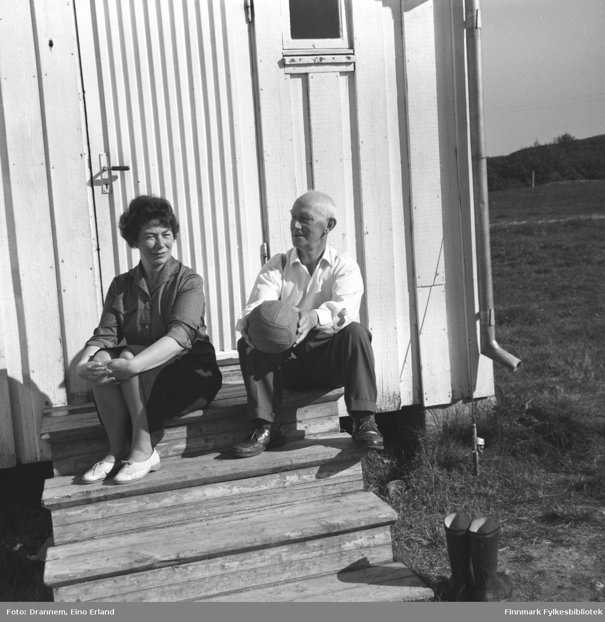 Jenny Drannem og Einar Jonassen sitter på trappa foran en bolig i Neiden.