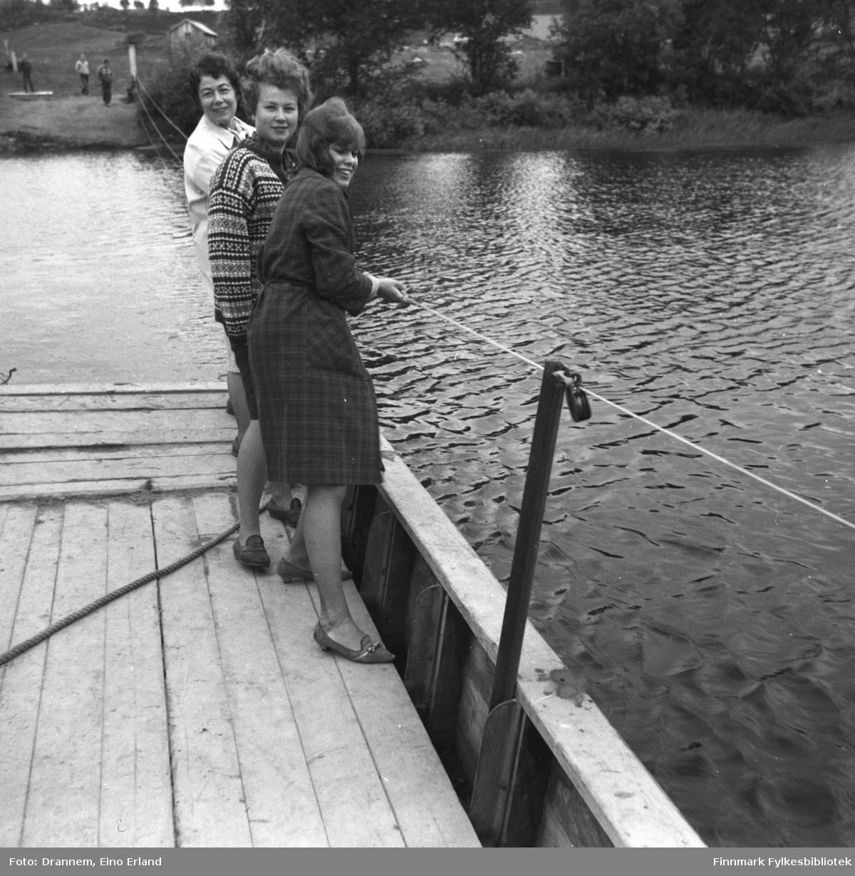 Tre personer på ferga over Neidenelva. Bakerst står Jenny Drannem, i midten Turid Karikoski og fremst står Marit Gabrielsen.