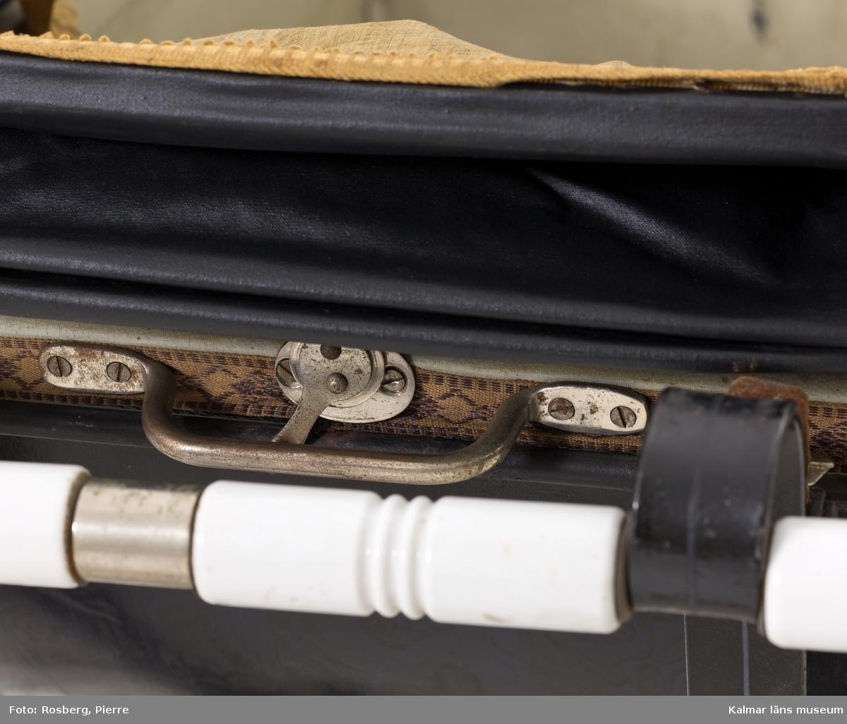 KLM 45797. Barnvagn, liggvagn. Stomme och hjul av svartlackerad metall, på stommen blå dekorlinjer. Gummiklädda hjul. Löstagbar vagnskorg med stomme av svartmålat trä med ljusblå dekorlinjer och fält målade i mörkare blå. På insidan är korgen klädd med vit galon. Vid korgens båda kortsidor handtag av vitt porslin. På vagnskorgens utsida ett vävt tygband av ylle i brun nyans. På ena kortsidan en liten metallskylt: AKTIEBOLAGET A.W. NILSSONS FABRIKER MALMÖ. Vagnen har en sufflett av svart galon med nedre kant av blått ylletyg. Upptill ett vävt tygband i gul nyans, på sidan ett handtag av vitt porslin. Vagnens ena fäste för suffletten är trasig och suffletten går därför inte att fästa ordentligt.
