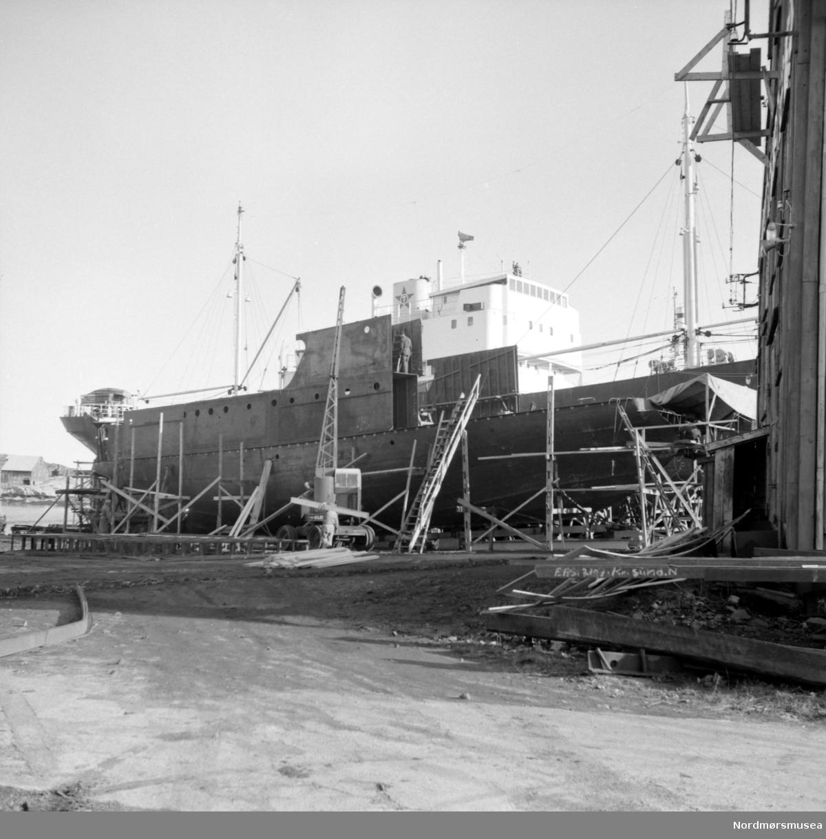 """Bildet viser B/F""""Norddalsfjord"""" Storviks Mek. Verksted bnr.14 på beddingen og med delvis oppbygd dekkshus.  """"Norddalsfjord"""" ble levert til Møre og Romsdal Fylkesbåtar 15. mars 1961 og hadde følgende hoveddimensjoner: L 31,20 m x B 8,55 m x D 3,35 m og hadde en tonnasje på 159 bruttoregistertonn. Fremdriftsmaskineriet består av 3 Volvo Penta turboladede dieselmotorer type TMD96 på til sammen 420 hk som via kilremdrift var koblet til et felles gir og propellaksel med vribar propell, slik at hver enkelt av motorene kunne kjøres separat. Fergen hadde 2 Bolinders vekselstrømsaggregater type 1052MG på 23 hk hver tilkoblet en generator på 17 kW. Fergen var utstyrt med elektrohydraulisk styremaskin. Fergen har plass til 18 personbiler og har sertifikat for 160 passasjerer. Forut er det innredet 6 lugarer for offiserer og restaurantpersonale og akterut en mannskapslugar for 4 personer og toppfarten er 11,4 knop og marsjfarten 10,5 knop. Ferga er verkstedets første nybygg etter B/F""""Trygge"""" som ble levert i 1938.  På den nye patentslippvogna klinkbygget i stål 1918, den største slippen mellom Bergen og Trondheim, ses lastebåten M/S""""Knoll"""" fra Ole T. Flakkes rederi og foran nybygget ses verkstedets mobilkran type Jones KL22, med egenlaget forlenget bom anskaffet ca. 1959.  Til venstre ses Høttnesbrygga ute på Høttnesset med det lille sorte røykerihuset like bak. Helt til høyre ses så vidt fronten av maskinverkstedbygningen, bygget etter brannen i februar/mars 1911 og revet på 1980-tallet, og til venstre foran nybygget ses sveiseplanet. Til høyre foran maskinverkstedet ses stålprofillager. I bakgrunnen ses Visnesbrygga på Skorpa. Bildet er fra 1960. Kilde: Peter Storvik. Fra Nordmøre museums fotosamlinger."""
