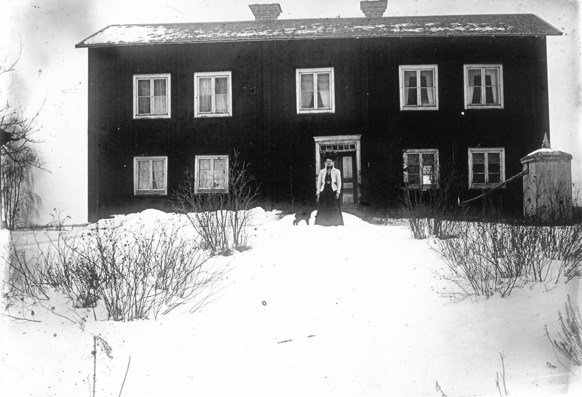 Kvinna framför bostadshus.