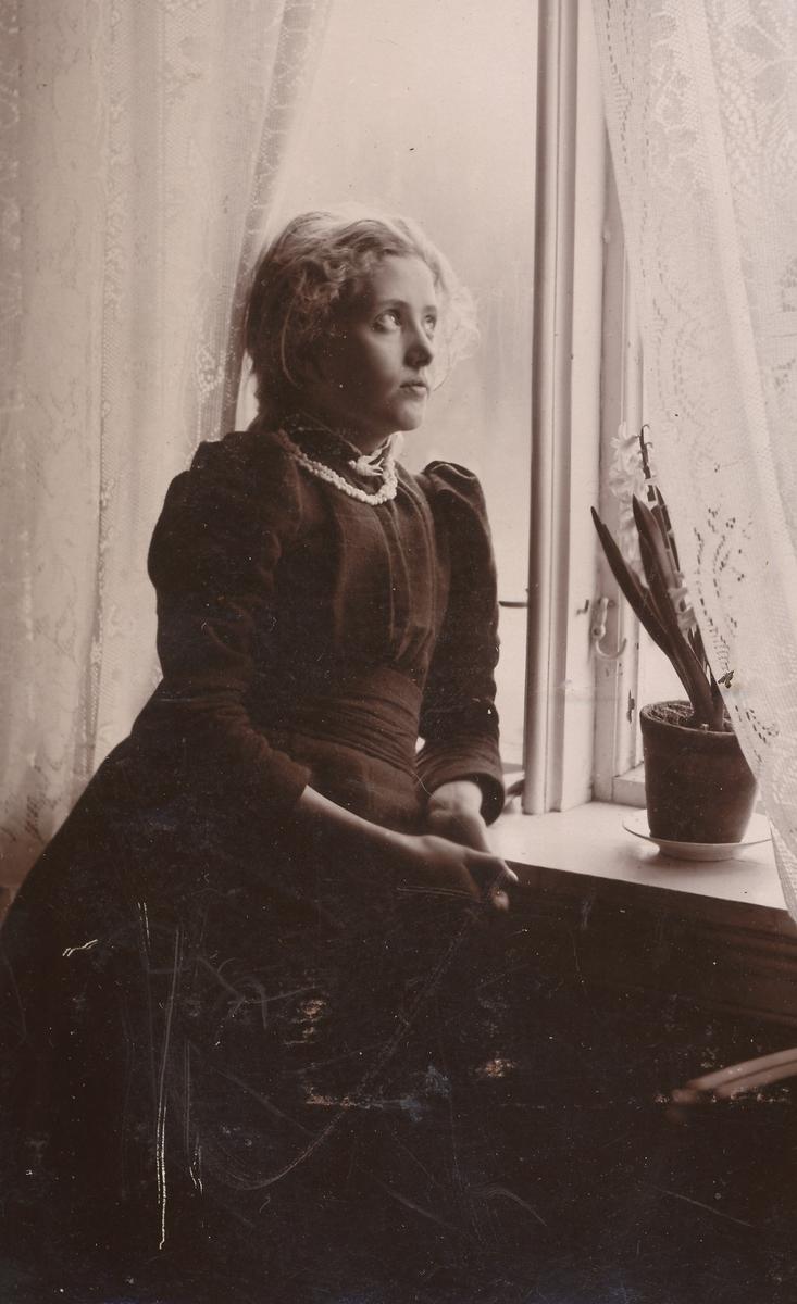 Portrett av ung pike ved vindu.