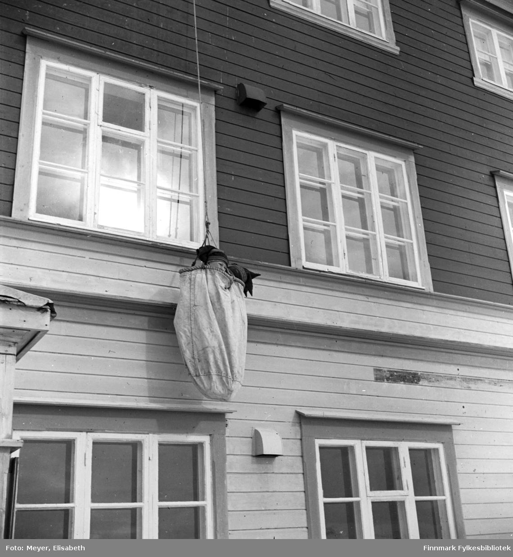 Brannøvelse på Kautokeino Skoleinternat. Johan Nils Peder Johansen Sara og en gutt til har fått plass i sekken som er festet til branntau i 3.etasje. Guttene henger og dingler på ytterveggen på vei ned.