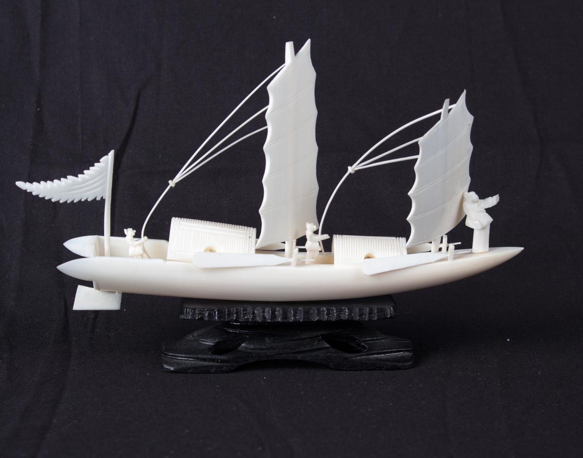 Modell av kinesisk fartøy utskåret i bein på sort sokkel. Skipsmodell med to master og seil, samt tre menn ombord. To par årer langs skutesiden. Vimpel akter.