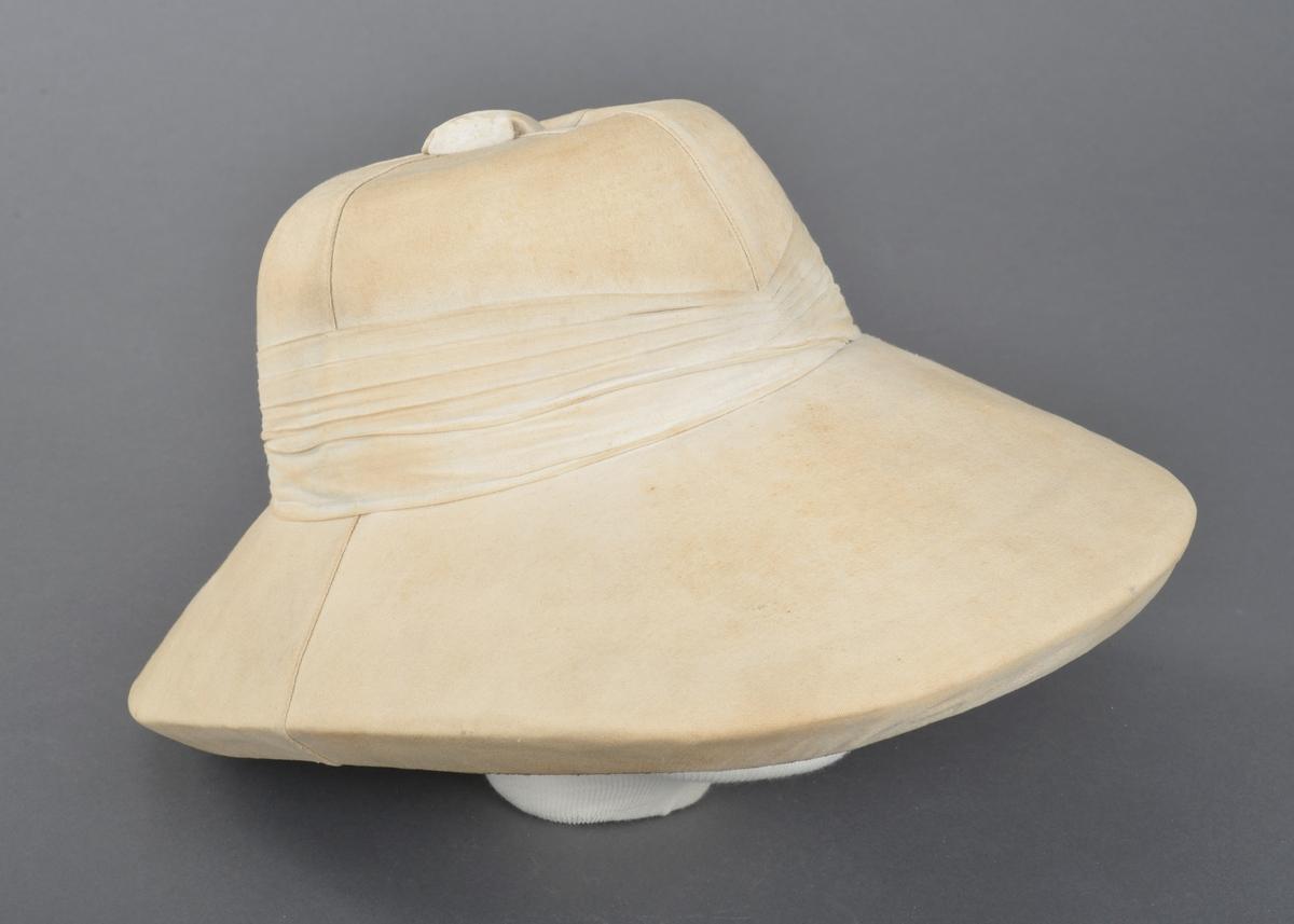 Hatt trekt med stoff. Pullen er sydd sammen av fire deler. Trekt knopp på toppen. Rundt pullen er hatten dekorert med flere lag med stoff. Pullen og bremmen er av lett og tykt materiale. Pullen er foret og i toppen er det trykt fabrikkmerke. Bremmen er foret med grønt stoff. Skinnkant er festet i nedere kant av pullen.