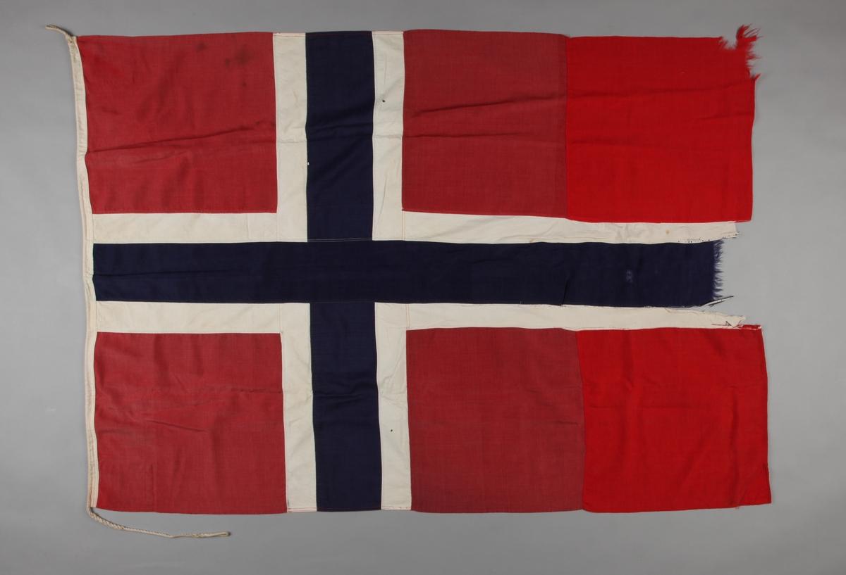 Norsk flagg fra DS DRAUGEN. Skader særlig på enden med hvitt og blått felt. Deler av rød tekstil er satt inn senere.