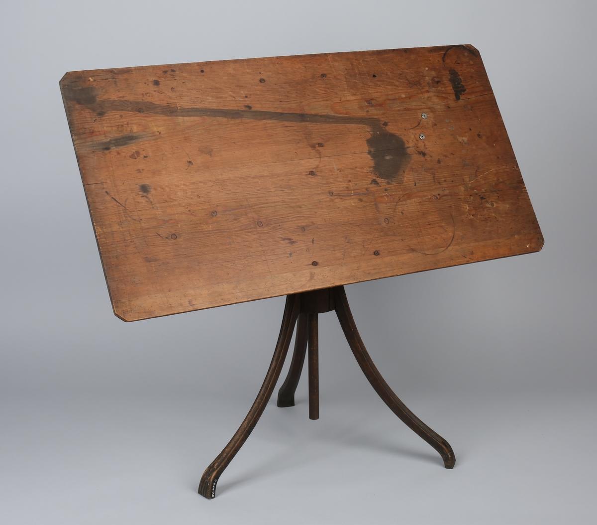 Tegnebord som har tilhørt Ananias Dekke. I tre med sokkelstativ i jern og tre med 3 stk. føtter. Kan reguleres i høyden.