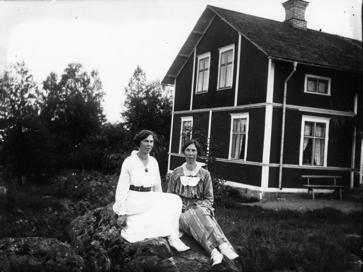 Två kvinnor framför husknut.