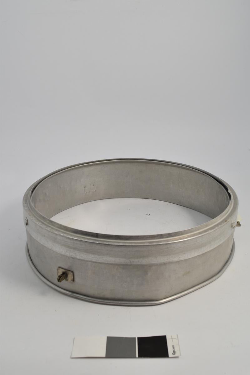 Form: Sirkulær kant. a): Pulverkar, k+b): til å holde siktene, c-j): sirkulære nettingsikter i forskjellige størrelse. Alt i metall. 11 deler.