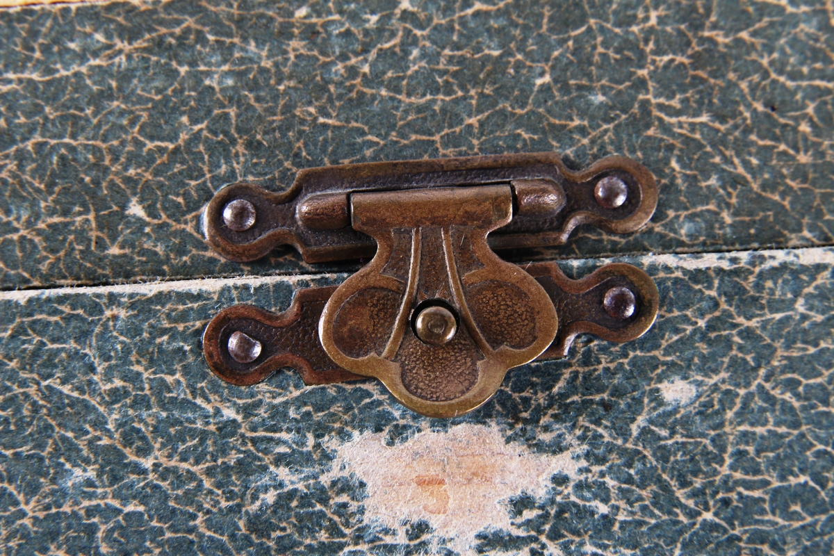 Smykkeskrin med hengsler og lås. Innsiden er foret med rødt silketøy. Et speil er festet på innsiden av lokket.