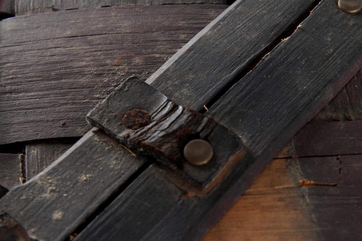 Brunmalt korg flettet av spon. En stor rund hank på midten og to lokk. Bare det ene kan åpnes.