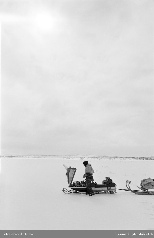 """Postfører Mathis Mathisen Buljo, bedre kjent som """"Post-Mathis"""" i samiske kretser, har stoppet for å fylle bensin på snøskuteren ute på Finnmarksvidda.   Fotograf Henrik Ørsteds bilder er tatt langs den 30 mil lange postruta som strakk seg fra Mieronjavre poståpneri til Náhpolsáiva, videre til Bavtajohka, innover til øvre Anárjohka nasjonalpark som grenser til Finland – og ruta dekket nærmere 30 reindriftsenheter. Ørsted fulgte «Post-Mathis», Mathis Mathisen Buljo som dekket et imponerende område med omtrent 30.000 dyr og reingjetere som stadig var ute i terrenget og i forflytning. Dette var landets lengste postrute og postlevering under krevende vær- og føreforhold var beregnet til 2 dager. Bildene gir et unikt innblikk i samisk reindriftskultur på 1970-tallet. Fotograf Henrik Ørsted har donert ca. 1800 negativer og lysbilder til Finnmark Fylkesbibliotek i 2010."""