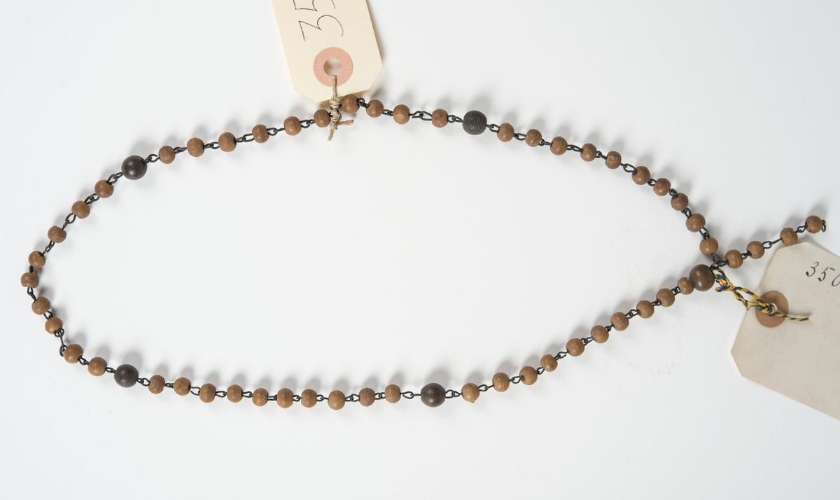 Halsband gjort av kulor av kokosskal. Var elfte kula är större och mörkare.