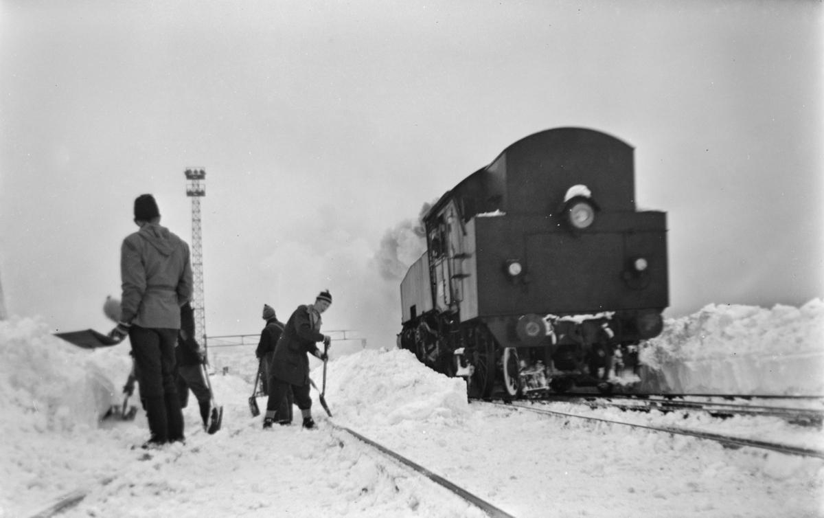 Snøryddingsmannskaper og snøryddingstog trukket av damplokomotiv type 32a, trolig nr. 291, på Trondheim stasjon.