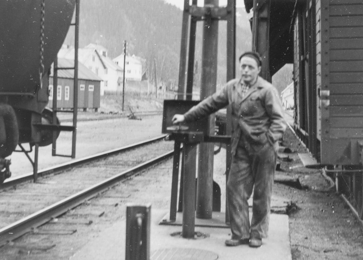Lokomotivstallbetjent Ole Schjødt fyller vann på damplokomotiv type 63a.