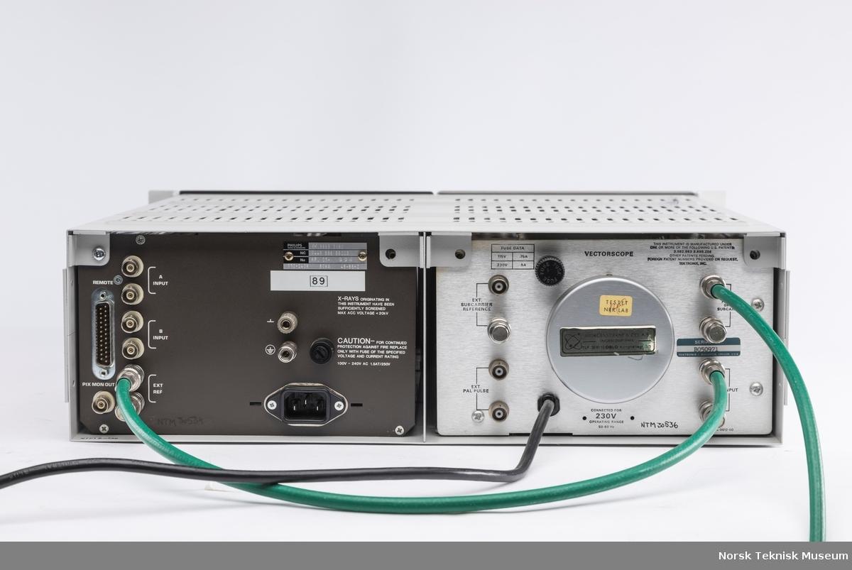 Rack med monitor og måleapparat med to grønne ledninger. Måleapparatet har ledning med støpsel.