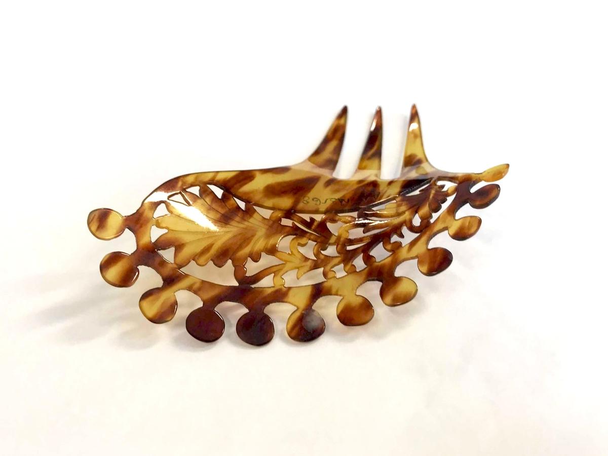 """Form: Kam med tre buede tinner.Overstykket er rundet og buet utover øverst, hvor øvre kant er forsynt med kant av sirkulære """"tagger"""". Ovalt buet felt med gren med vifteformet blad i gjennombrutt arbeid."""