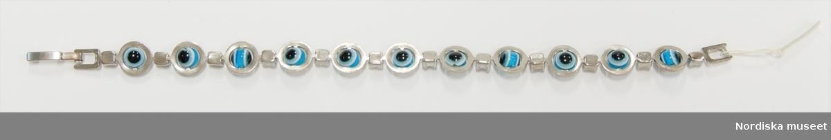 Armband av vitmetall och plast (?). Bestående av 11 runda plastpärlor i svart/vit/blå infattade i ringar av vitmetall (pärlorna är rörliga i infattningen) mellan varje ring en liten fasettslipad plastbit infattad i vitmetall. I ändarna låsanordning. Anm. 8 st fasettslipade plastbitar saknas. /Leif Wallin 2017-09-15