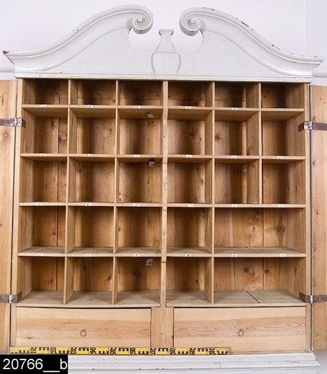 Anmärkningar: Skåp på fot, gråmålat, 1700-talets senare hälft.  Överdel: Framskjutande kälat och rundat krön med voluter i mitten. En skuren balusterdocka i halvrelief sticker fram mellan voluterna. Spegelförsedda pardörrar med gerade och profilerade lister. Tre nyckelskyltar i järn på höger dörr. Invändigt fem hyllor, vardera indelade i sex fack (bild 20766__b). På höger dörr sitter en plan över vad som har förvarats i respektive fack (bild 20766__d). Planen är tidigast från år 1857 då det finns anteckningar om att handlingar från detta år har funnits i skåpet. Invändigt ett lås och tre hankar och hankfästen i järn. Nyckel i järn (bild 20766__e). H:1815 Br:1660 Dj:535  Underrede: Överst framskjutande och profilerade lister. Kontursågad sarg. S-svängda ben. H:580 Br:1610 Dj:510  Tillstånd: Skåpet har haft fyra olika färger i följande ordning: gult, brunt, grått och sist grått igen (bild 20766__c). Två lås och tillhörande nycklar saknas.  Historik: Från Västmanlands Regemente.