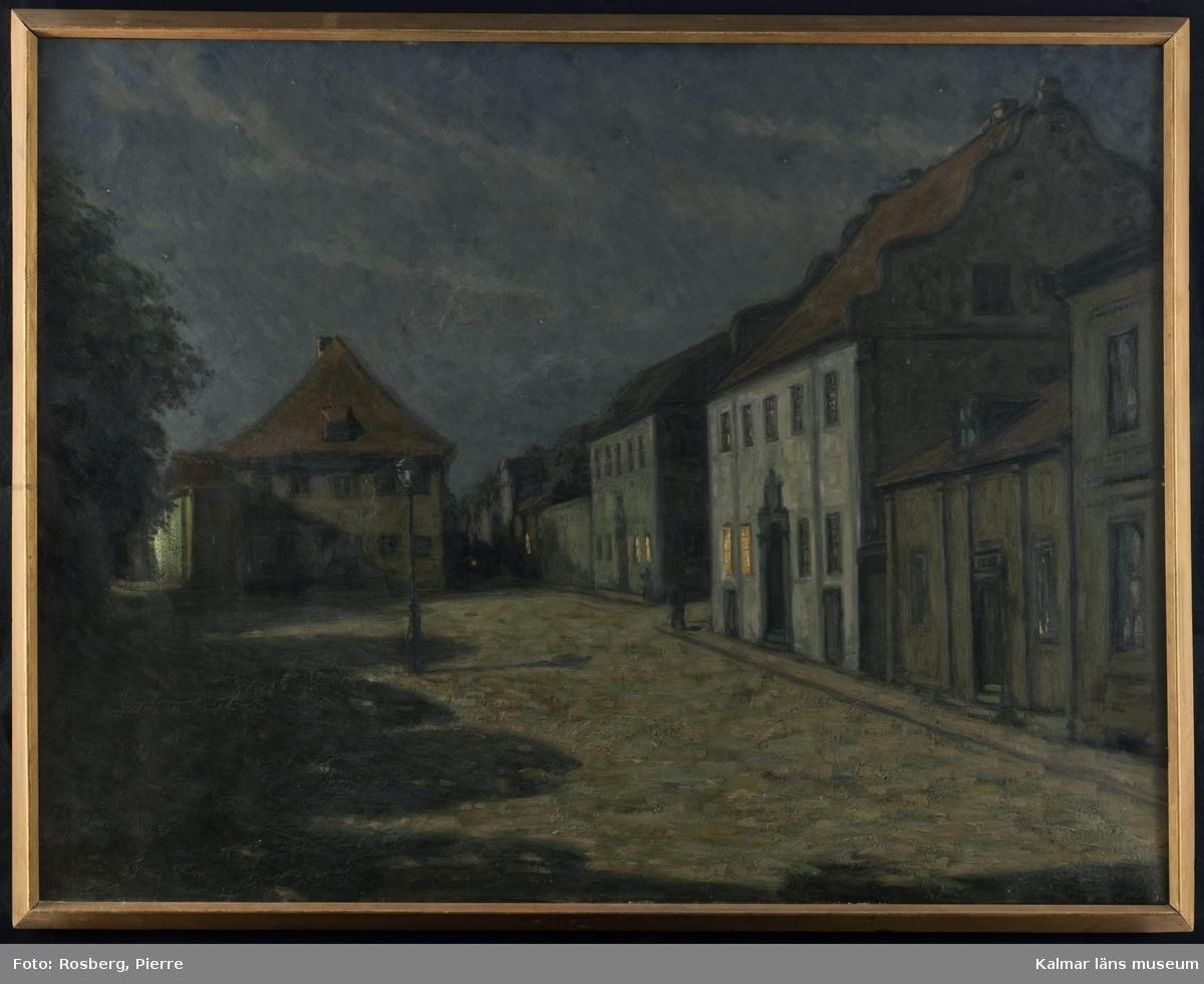 Lilla Torg i Kalmar, i kvällsljus, vilket bildar starka skuggor. Domprostgården, Länsresidenset och Damska huset ramar in torget med en släckt lykta mitt på torget.