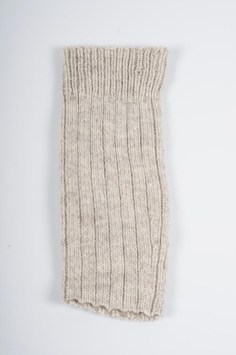 Ett par leggvarmere. Antakeligvis avklipte strømper. Strikket i ribbestrikk i lyst gråmelert garn. Vrangbord i ribbestrikk med 1 rett og 1 vrang. Resten er strikket med 3 rette og 1 vrang.