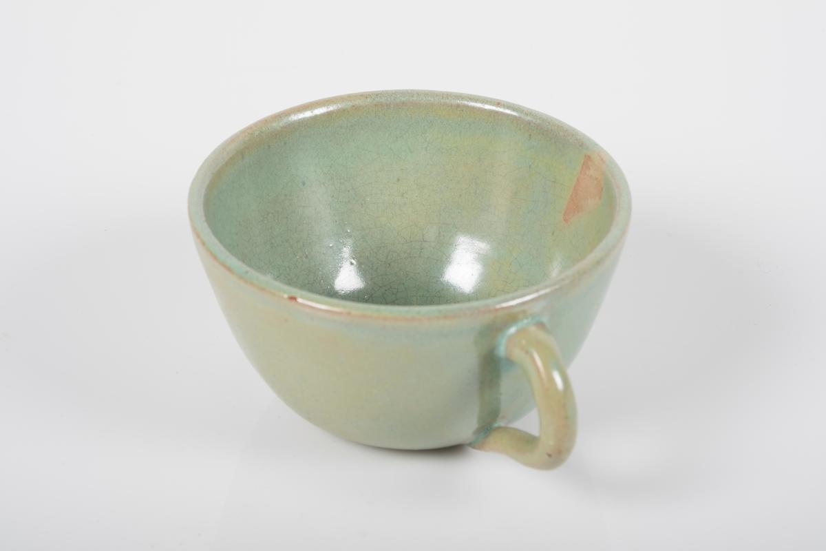 Kopp keramikk med grønn lasur. Buet hank på koppen. Bunnen har matt overflate.