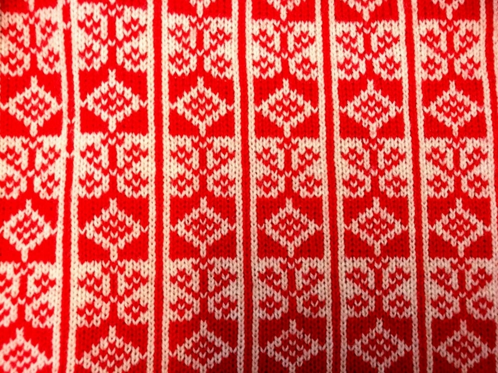 Bingestickad kappa stickad i rött och vitt 2-trådigt ullgarn. 9cm krage i rött med virkad kant runt. 3,5 cm bred knappslå , 13 kanppar och knapphål. Helfodrad med röd sidentaft.