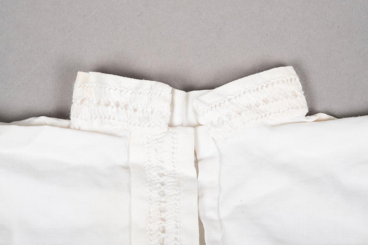 """Hvit """"bunadsskjorte"""" i bomull med kinakrage og hullbroderi langs kantene."""