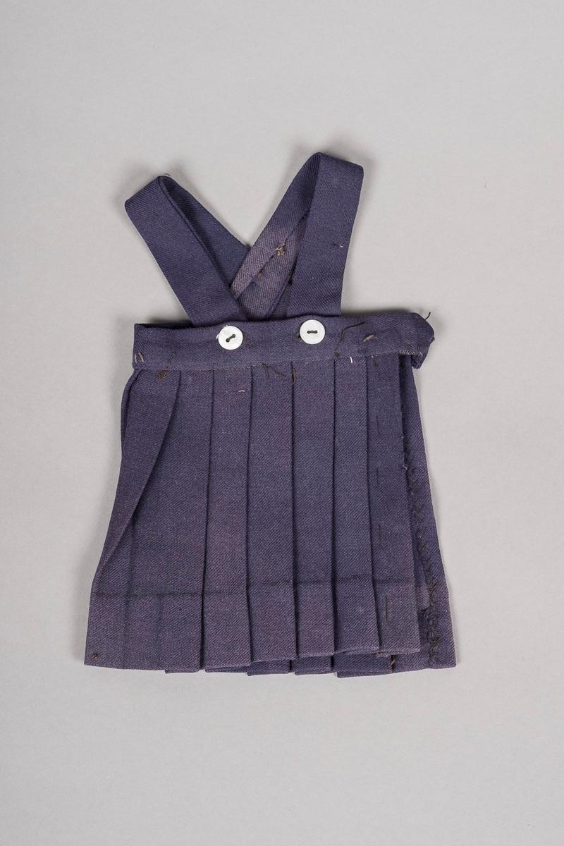 Mørkeblå ullkjole med plisséskjørt og seler. Selene er festet med hvitskimrende knapper.