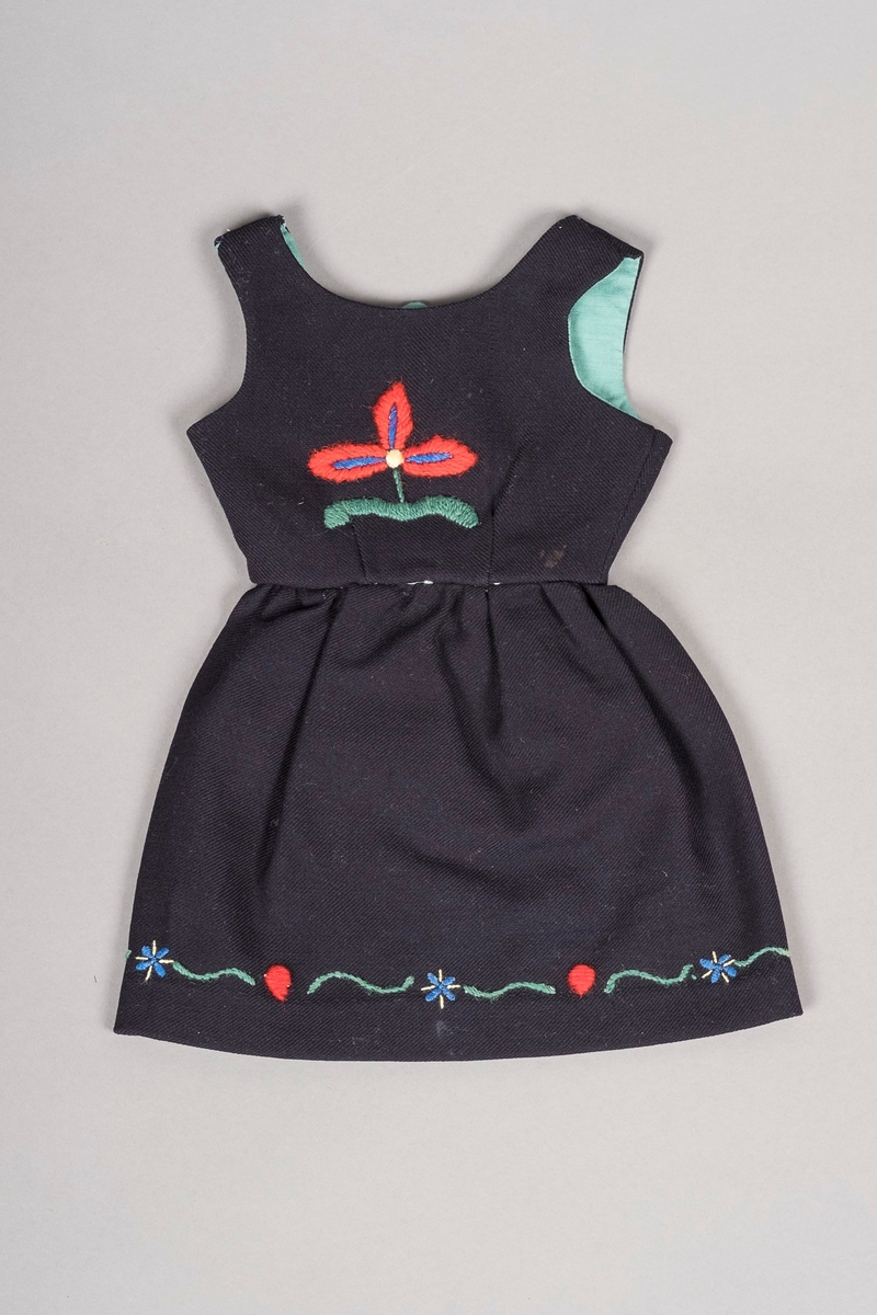 """Mørkeblå """"dukkebunad""""/ -festdrakt, med blomsterbroderier i blått, grønt, rødt og lysegult. To stor blå blomster på forsiden, en stor rød blomst på ryggen. Livet til stakken er foret i blågrønt bomullsstoff, og har fire """"tinnknapper"""" kaget av blikkboks-materiale."""