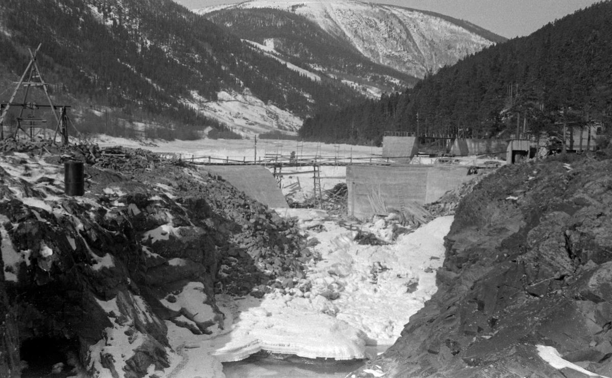 Bygginga av ny inntaksdam ved Eidefoss kraftverk i Ottavassdraget i 1952 (Vågå kommune).  Fotografiet er tatt i motstrøms retning, over et nesten tørrlagt elveløp gjennom en berghammer.  Damarbeidet ble, typisk nok, utført i overgangsfasen mellom vinter og vår, da vannføringa var minimal.  Ottaelva i bakgrunnen var fortsatt islagt.  Stengselet for damåpningen var ennå ikke kommet på plass.  Det første kraftverket ved Eidefossen ble bygd i 1916-17.  Den nye betongdammen fra 1952 ble støpt med henblikk på å utvide magasinkapasiteten, slik at en kunne installere nok et aggregat i kraftstasjonen.