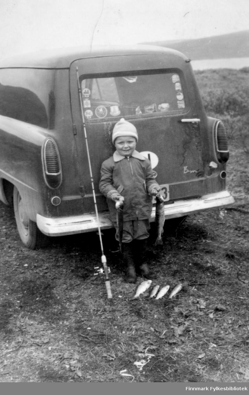 Barn med fiskefangst fotografert bak en Ford Taunus 15M varebil. Kfr 15M-logo står nederst til høyre bak på døren. Barnet står med fiskestang og flere fine ferskvannsfisker liggende på bakken. Barnet holder en fisk i hånden. Langs kanten av bilruta er det klistrert på mange merker med stedsnavn. Det var vanlig å kjøpe slike på bensinstasjoner når man var ute på ferieturer. Bildet kan være tatt i perioden 1955-1970.   Familiealbum tilhørende familien Klemetsen. Utlånt av Trygve Klemetsen. Periode: 1930-1960.