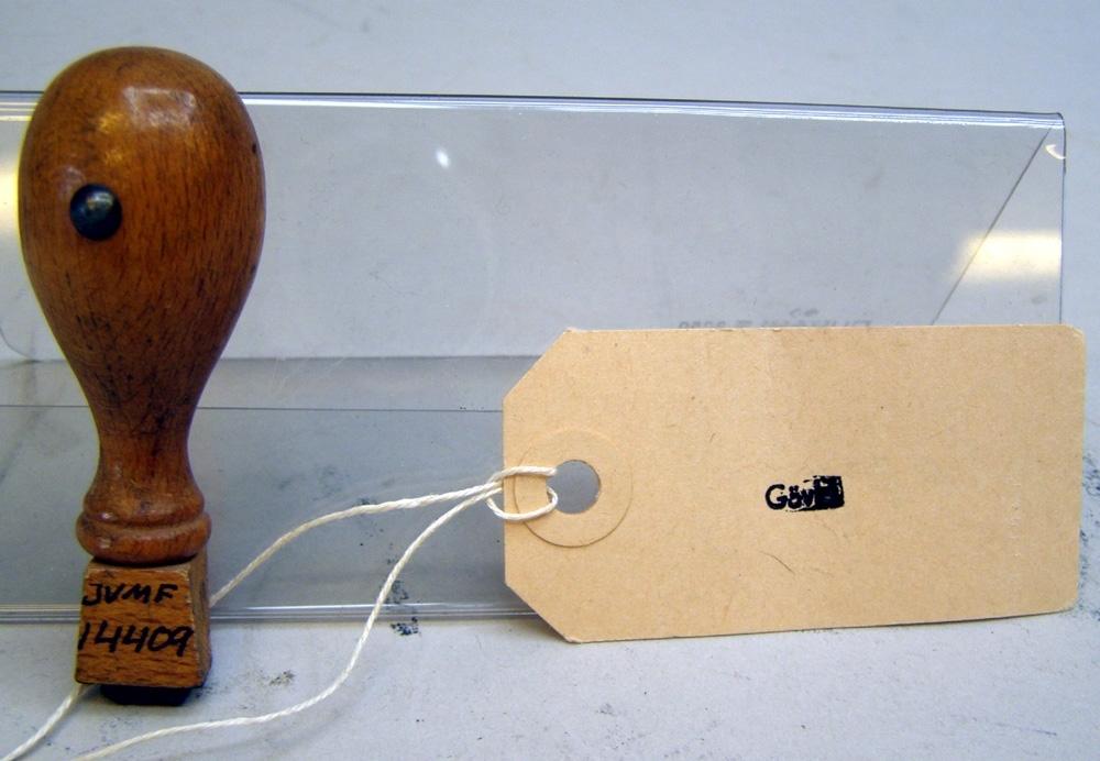 """Stämpel med rektangulär stämpelplatta av gummi och svarvat brunt träskaft. Text: """"Gävle""""."""