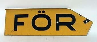 """Skylt av gul reflekterande plåt med svart text: """"VARNING FÖR TÅG"""". Skylten består av fyra plåtar med text och en hållare för montage i kryss. Den gula färgen har glaspärlor som ljusreflekterande materiel. """"Krysset"""" har ingjutet ÖR 9183 på baksidan. Ihopmonterat har krysset måttet bxh 560x340 mm. Plåtarna är gråmålade på baksidan."""