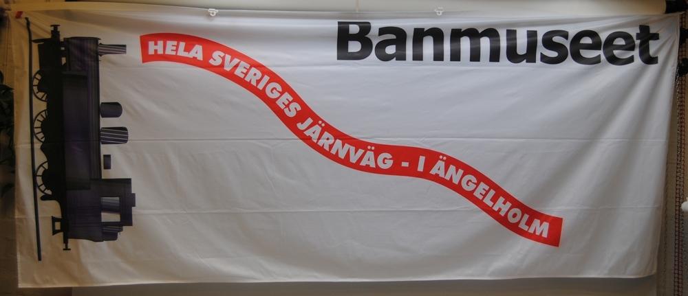 """Vit flagga med dekoration av ånglok och text. Längst upp står det """"Banmuseet"""" i svart. Nedanför detta står det """"HELA SVERIGES JÄRNVÄG - I ÄNGELHOLM"""" med vit text i ett rött böljande språkband. Utmed vänster kortsida är det ett svart ånglok. Flaggan har plastöglor utmed den övre långsidan."""