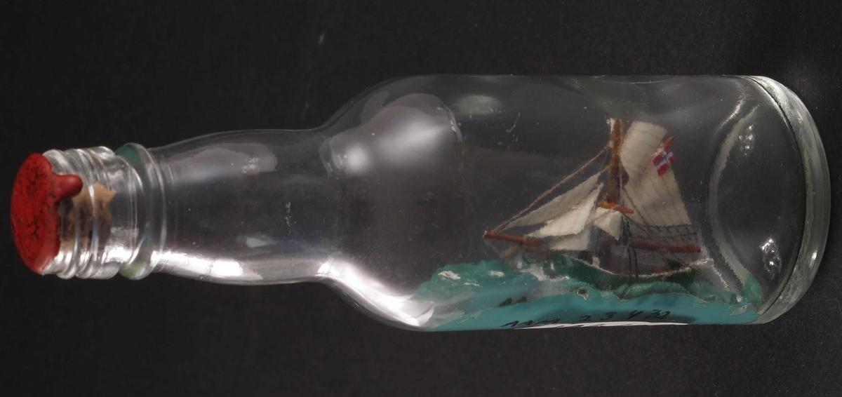 """Miniatyr flaskeskute: Jakten """"Gjøa"""".  Glass, klart. Kork. rød lakk. Innstøpt i bunnen:  MG  (Moss Glassverk)  12. Grønnmalt skrog, grønn sjø, norsk flagg."""