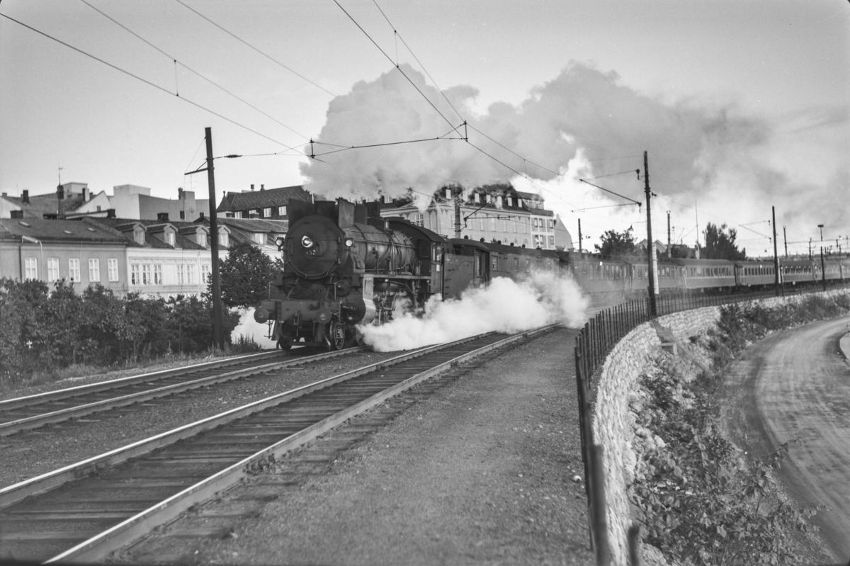 Persontog fra Oslo Ø til Otta, Pt. 307 kjører ut fra Hamar stasjon. Toget trekkes av damplokomotiv type 31b nr. 452..
