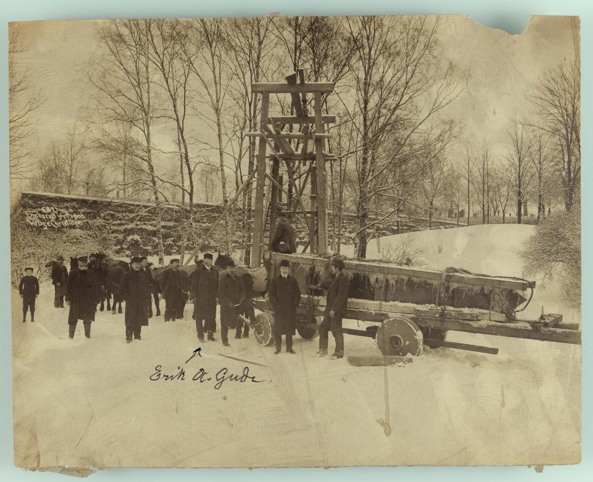 Henrik Ibsens gravmonument (obelisk) transporteres til kirkegården. Eirik A. Gude sammen med arbeidere.