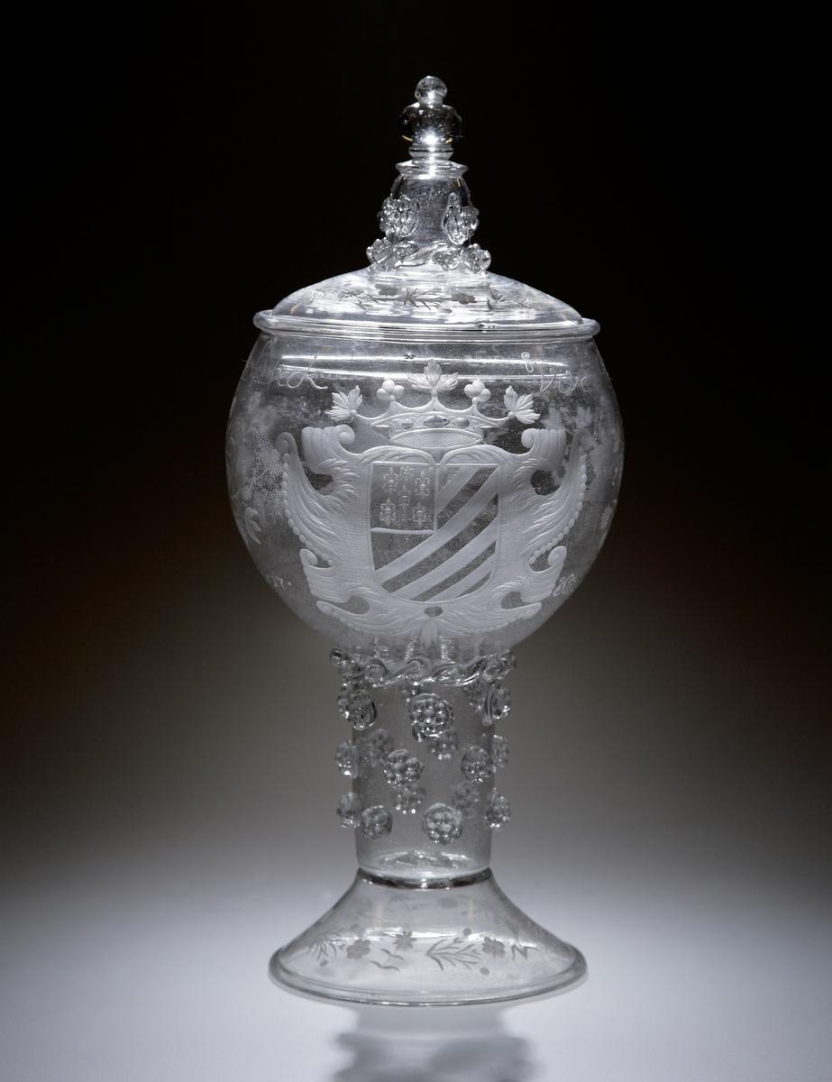 """Hyllningsbägare med lock. Ursprungligen gåva till Jacobus von Melle* (1659-1743) år 1717, pastor i St Mariakyrkan i Lübeck. Remmare av generösa mått. Den med text, vapensköld, nordstjärna och blomsteruppsatser graverade kupan fortsätter ner i det med påklippta """"hallon"""" utsmyckade benet. Mellan kupa och ben en påklippt och skulpterad girlang. Foten är blåst och driven, samt utsmyckad med graverade utströdda blommor.    Text på kupans övre del: """"Vivat Herr Magister Jacobus: a: Melle Pastor: a: St Maria inn Lübeck. Solches wünschet. B B. Stockholm. d. 9. September A:o 1717"""".   """"B. B"""" kan eventuellt stå för Berendt Bruns - svärson till Jacob Melle, enl. meddelande från Danzig, 1938-12-25. Inskrivet i huvudkatalogen 1935.  *Se bifogade bilder på den yngre och äldre Jacobus von Melle."""